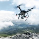 Modern drone flies in the mountains. Dark drone in the air against the backdrop of a mountain landscape stock photography