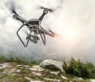 Modern drone flies in the mountains. Dark drone in the air against the backdrop of a mountain landscape stock photo