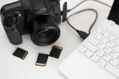 Modern camera connected with computer and memory cards on the ta. Modern dslr camera connected with computer and memory cards on the table royalty free stock photography