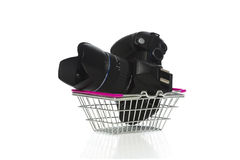 Camera and lens in a shopping basket. Modern dslr camera, lens and lenshood in a metal shopping basket on a white background conceptual of retail, consumerism Royalty Free Stock Photo