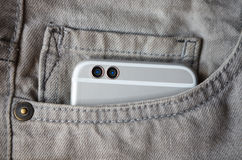 Modern dual camera smart phone in jeans pocket Stock Photography