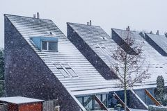Modern dutch pointy rooftops covered in snow, Modern neighborhood during winter season, snowy cold weather in the Netherlands stock photography