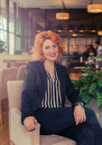 Modern and dynamic woman. Beautiful, red-haired woman sitting in a chair in a restaurant Stock Image