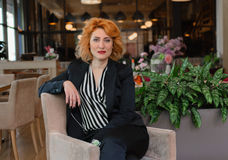 Modern and dynamic woman. Beautiful, red-haired woman sitting in a chair in a restaurant Royalty Free Stock Image