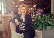 Modern and dynamic woman. Beautiful, red-haired woman sitting in a chair in a restaurant Stock Images