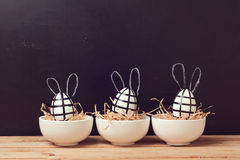 Modern Easter egg decorations with bunny ears on chalkboard. Creative Easter background. Stock Image