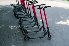Modern eco electric city scooters for rent outdoors on the sidewalk. Alternative tourism, transportation around the city, bike. Replacement service. E-scooters royalty free stock images