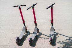 Modern eco electric city scooters for rent outdoors on the sidewalk. Alternative tourism, transportation around the city, bike. Replacement service. E-scooters stock image