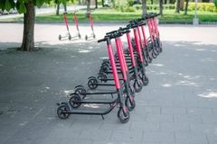 Modern eco electric city scooters for rent outdoors on the sidewalk. Alternative tourism, transportation around the city, bike. Replacement service. E-scooters stock images