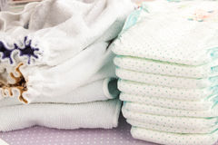 Modern eco stacks of cloth diapers and disposable diapers, pampers, selective focus close-up on bright background Stock Image