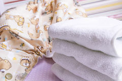 Modern eco stacks of cloth diapers and replacement bushings selective focus close-up on bright background Royalty Free Stock Images