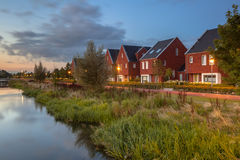 Modern ecological suburban street. Long exposure night image of a suburban Street with modern ecological middle class family houses with eco friendly river bank Royalty Free Stock Photo