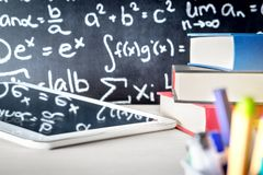 Modern education and e learning tools in school classroom table. Stack of books, tablet and pens with blackboard full or writing. Digital teaching and studying royalty free stock photography
