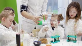 Children do an experiment in a chemistry lesson. modern education
