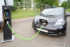 Modern elbil som laddas upp på elektrisk uppladdning Fotografering för Bildbyråer