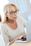 Modern elderly woman sitting in front of laptop Stock Photography