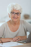 Modern elderly woman using laptop Stock Photos