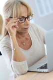 Modern elderly woman using laptop Stock Images