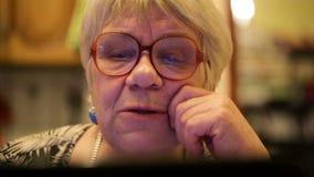 Modern elderly woman using skype. Close-up shot of elderly woman having emotional skype talk using laptop stock video