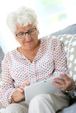 Modern elderly woman using tablet Royalty Free Stock Photos
