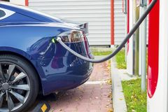 Modern electric car plugged to charging station in a parking lot. With leaves all around stock photo