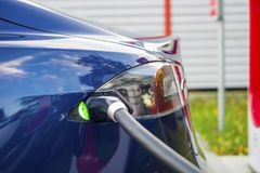 Modern electric car plugged to charging station in a parking lot Stock Photos