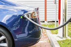 Modern electric car plugged to charging station in a parking lot Royalty Free Stock Image