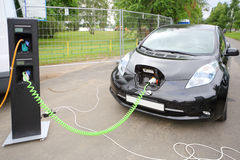 Modern electric car recharged at electrical charging Stock Image