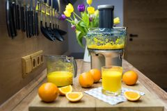 Modern electric juicer, oranges and freshly pressed juice on kitchen counter. Healthy lifestyle and detox concept. New year`s res Royalty Free Stock Photo
