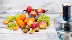 Modern electric juicer and various fruit on kitchen counter, healthy lifestyle detox concept. Royalty Free Stock Photos