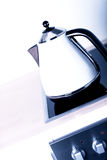 Modern electric kettle on cooktop Royalty Free Stock Photography