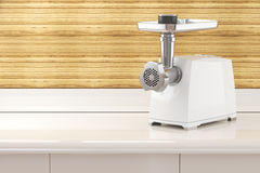 Modern electric meat grinder on a table in the kitchen room inte Royalty Free Stock Images