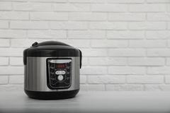 Modern electric multi cooker on table near brick wall. Space for text royalty free stock image