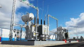Electric substation with power lines and transformers on day