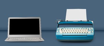 Old electric typewriter with laptop on blue table background Royalty Free Stock Image