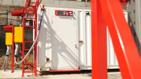 Modern electrical substation and red supports on foreground. Modern electrical distribution substation building with meter over door and red supports on stock video footage