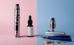 Modern electronic cigarette with e liquid bottle and ac. Cessories for vape devices. creative e cigarette background royalty free stock image