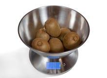 Kitchen Scales with Kiwis. Modern electronic metal kitchen weighing scales with kiwi fruits royalty free stock photos