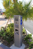 Modern Electronic Parking Meter. LAUDERDALE-BY-THE-SEA, FL, USA - APRIL 7, 2014: Closeup of an electric parking meter with signage in the shade of palm trees and Stock Images