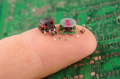Small electronics components on human finger. Modern electronics surface mount components in comparison to human finger royalty free stock images