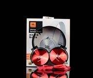 Red JBL headphones with box on black background. Modern, elegant looking JBL headphones. The rich red color gives them unique look. The sound is clear and the royalty free stock photos