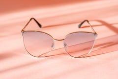Modern elegant metallramsolglasögon på moderiktig rosa pappers- bakgrund i solljus Lekmanna- l?genhet semester och partibegrepp arkivbild