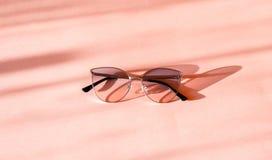 Modern elegant metallramsolglasögon på moderiktig rosa pappers- bakgrund i solljus Lekmanna- l?genhet semestrar den tropiska somm arkivfoton