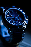 Modern elegant watch in blue tone. A blue tone image of an elegant male wrist watch stock images