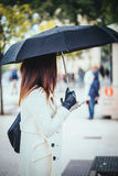 Modern and Elegant woman with umbrella at the city, using mobile Royalty Free Stock Photo