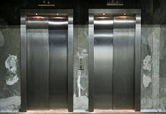 Modern elevator. New elevator doors in stainless steel with rough walls Royalty Free Stock Images