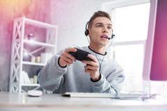 Modern emotionell tonåringkänsla, medan spela hans favorit- videospel royaltyfria bilder