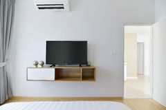 Modern Empty bedroom with led tv on white wall and wooden shelf Stock Image