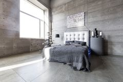 Modern empty bedroom in loft style with grey colors and wooden hand made Christmas tree with presents. Bed with grey blanket stock photography