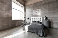 Modern empty bedroom in loft style with grey colors and wooden hand made Christmas tree with presents. Bed with grey blanket Royalty Free Stock Image